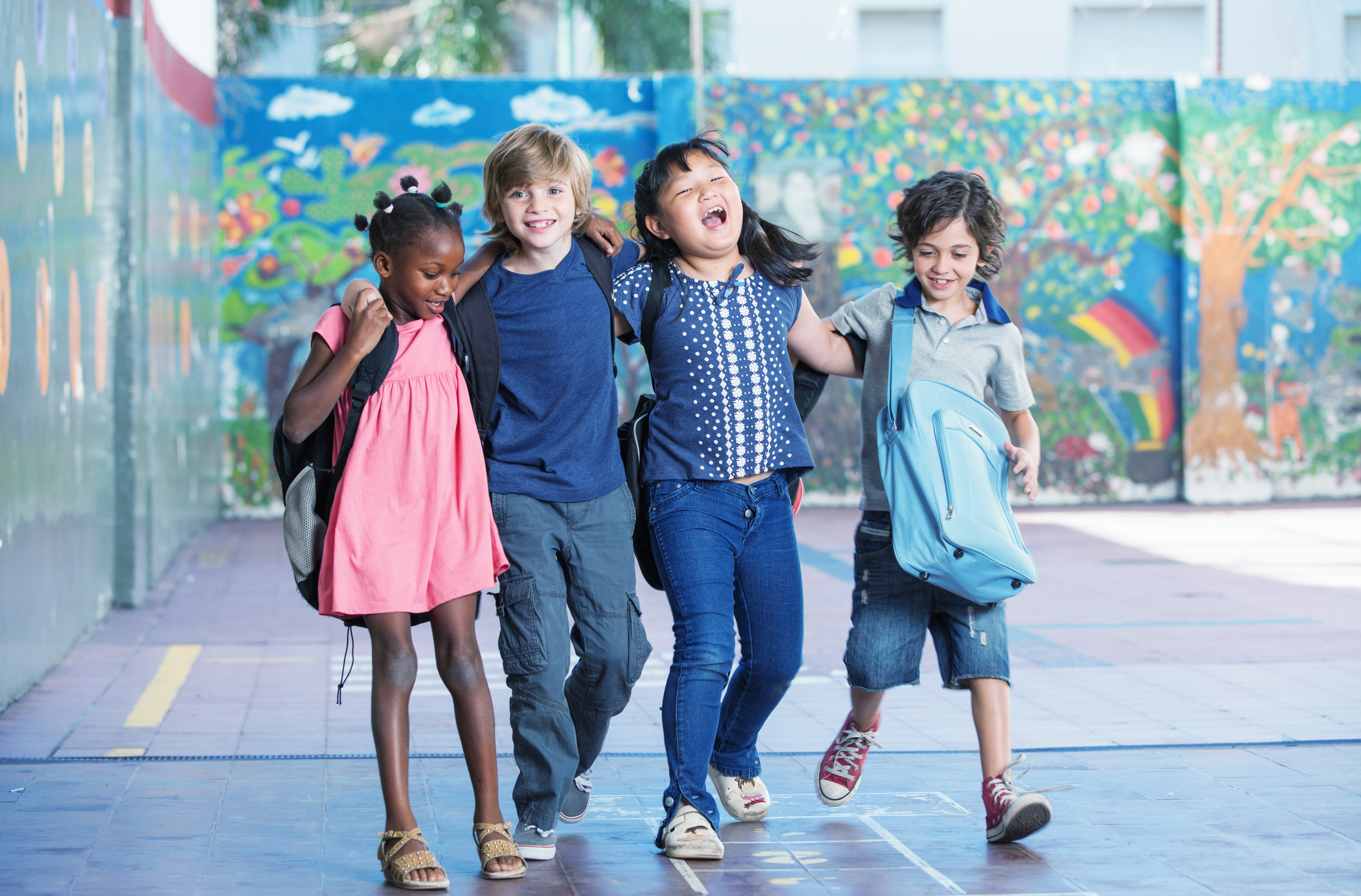 Happy kids embracing and smiling in the elementary schoolyard. Interracial friendship.